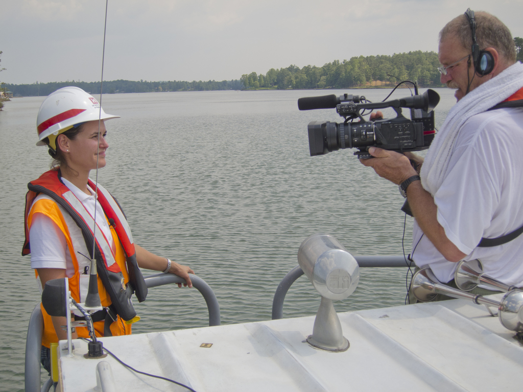Tornado - Dadeville, Ala. , July 13, 2011 -- U. S. Army Corps of Engineer Krista Rossow (resident engineer) provides an on-cmaera video explantation of wet debris removal on Lake Martin, Alabama (near Dadeville) to Willis Boyd, FEMA Video Specialist. FEMA monitors the quality, accuracy and consistency of wet debris removal in/on Lake Martin with the assistance and expterise of the Army Corps of Engineers. Photo by Christopher Mardorf / FEMA.