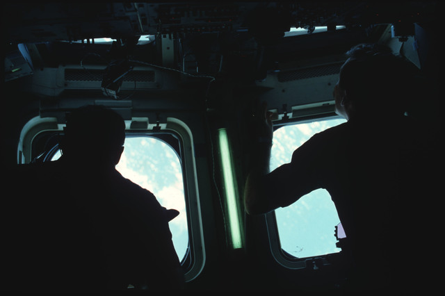 41B-03-093 - STS-41B - Two crewmembers are silhouetted against the aft flight deck windows