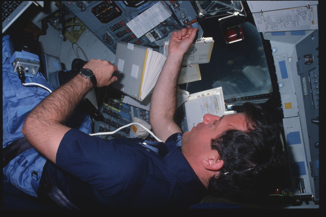 41C-01-032 - STS-41C - Mission specialist Terry Hart reviews checklist on flight deck