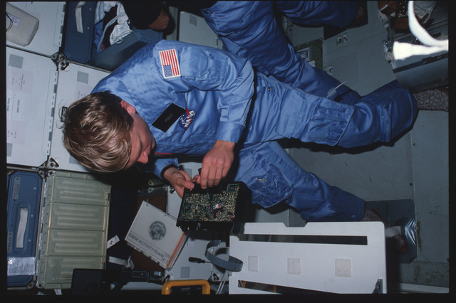 41C-04-144 - STS-41C - Mission specialist Nelson examines shuttle hardware
