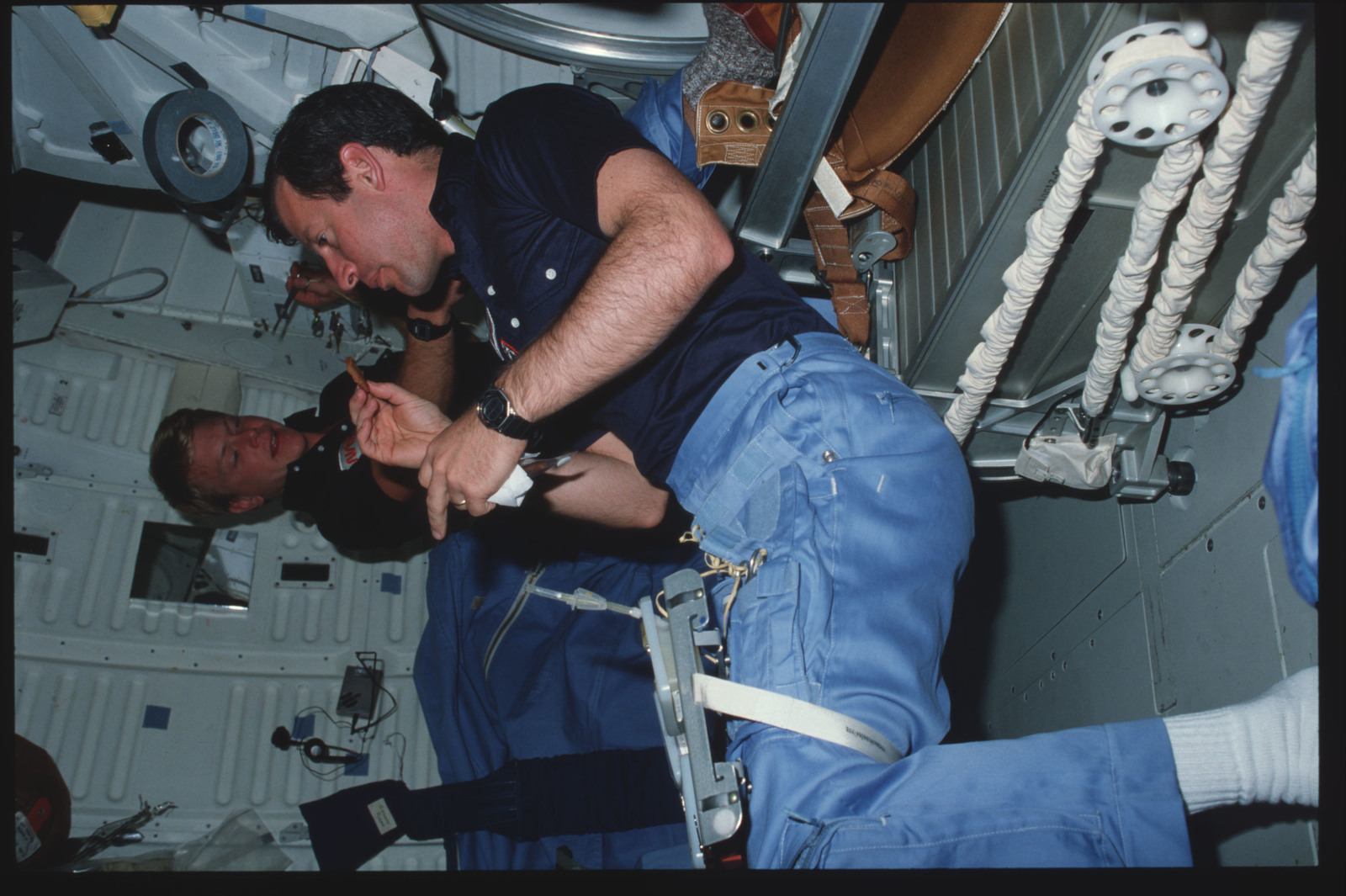 41C-07-249 - STS-41C - Candid views of STS-41C crew preparing food on middeck