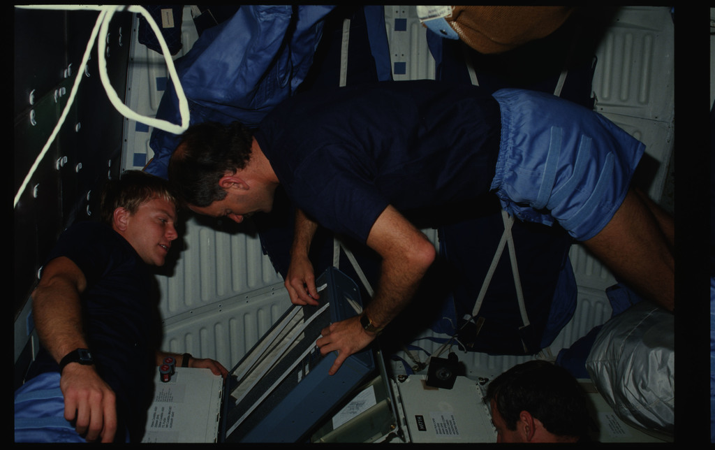 41C-08-281 - STS-41C - Astronaut van Hoften packs camera accessories on middeck