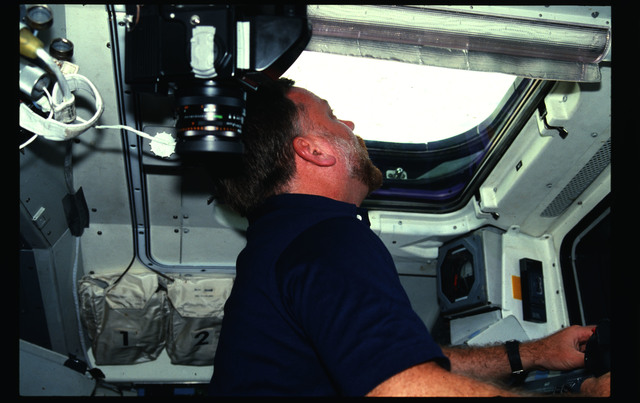 41G-01-020 - STS-41G - Scully-Power looks out overhead window in FD during 41G