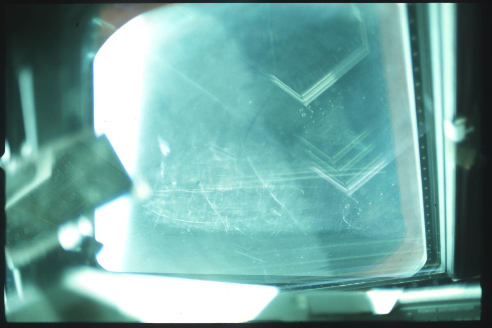S01-07-514 - STS-001 - Crew compartment flight deck window debris,damage,streak documentation