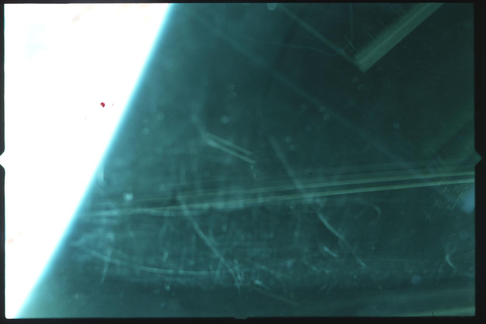 S01-07-517 - STS-001 - Crew compartment flight deck window debris,damage,streak documentation