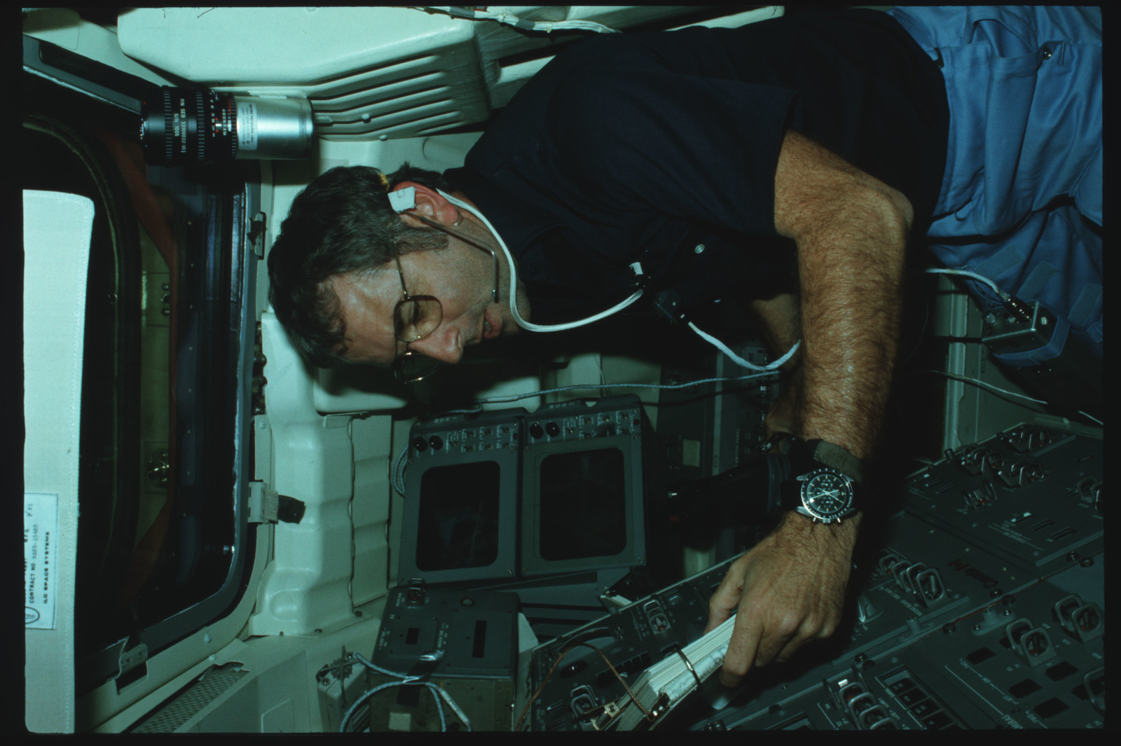 S02-02-876 - STS-002 - Pilot Truly reviews checklist and monitors CCTV screens on Aft Flight Deck