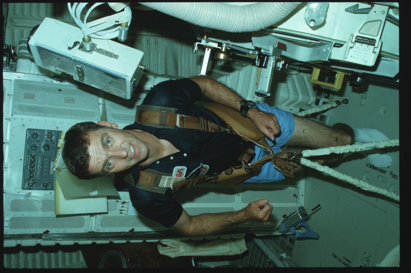 S02-02-884 - STS-002 - Commander Engle exercises on middeck using exerciser restraint harness