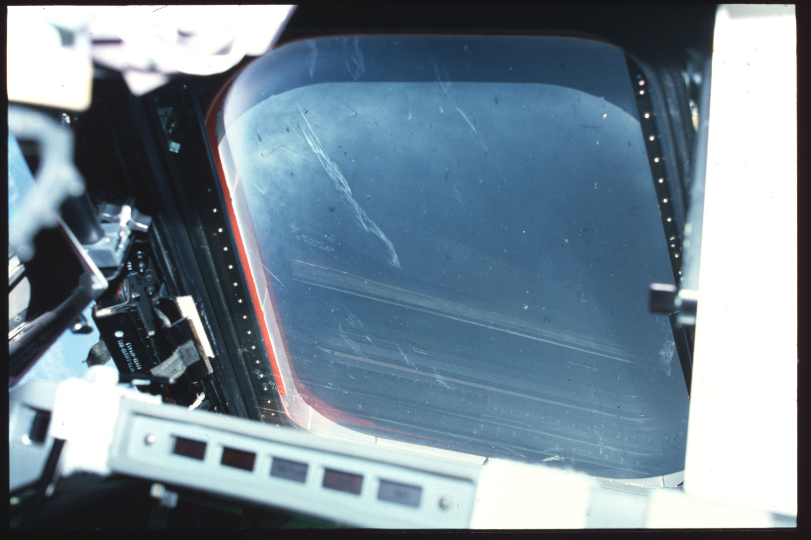 S03-19-001 - STS-003 - Crew compartment flight deck window debris, damage, streak documentation
