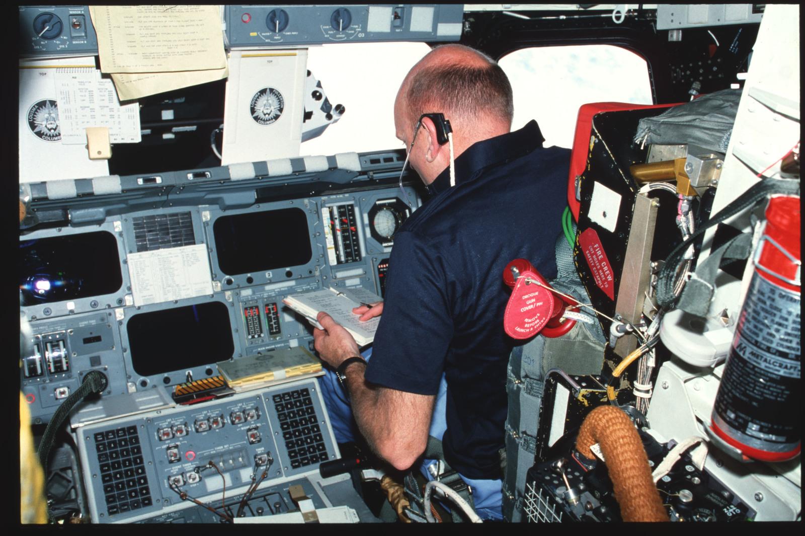 S03-22-130 - STS-003 - Pilot Fullerton reviews FDF checklist at forward flight deck pilots station