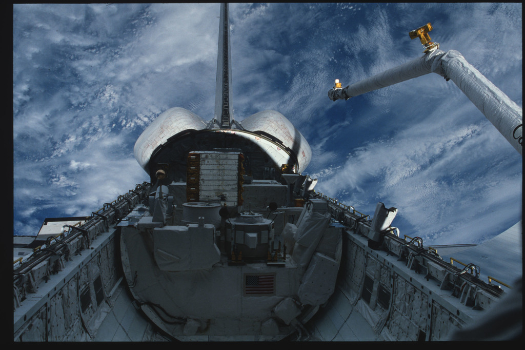S03-23-152 - STS-003 - RMS arm deployed above PLB with orbiter tail, Earth's surface in background