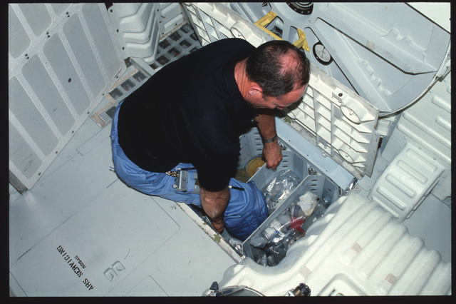 S03-25-233 - STS-003 - Commander Lousma stows trash bags in middeck CO2 Absorber Stowage volume