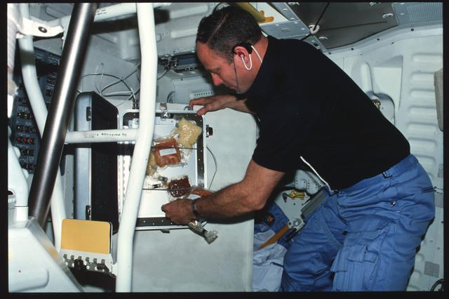 S03-26-266 - STS-003 - Commander Lousma prepare meal on middeck