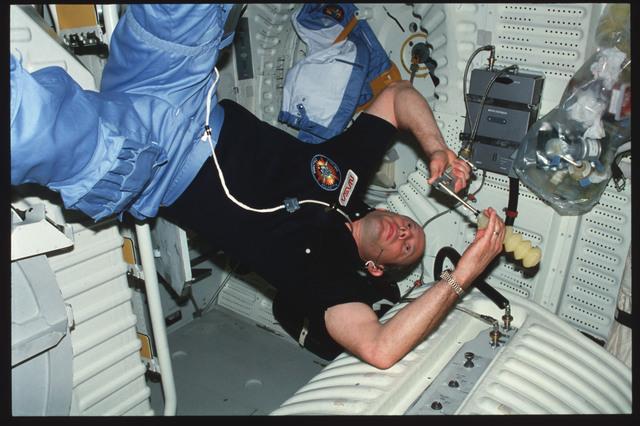 S03-26-267 - STS-003 - Commander Lousma prepare meal on middeck