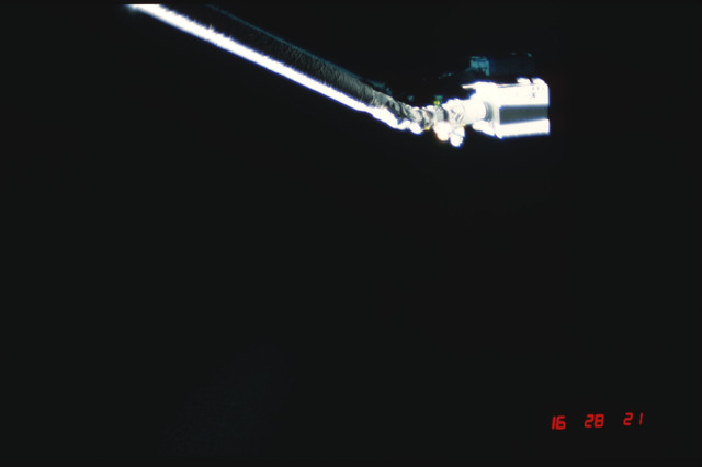 S04-20-020 - STS-004 - IECM grappled by RMS and positioned above payload bay