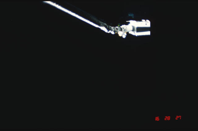 S04-20-021 - STS-004 - IECM grappled by RMS and positioned above payload bay