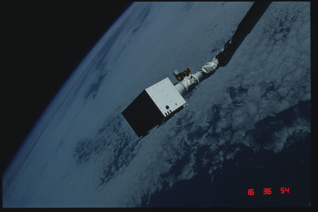 S04-20-026 - STS-004 - IECM grappled by RMS and positioned above payload bay
