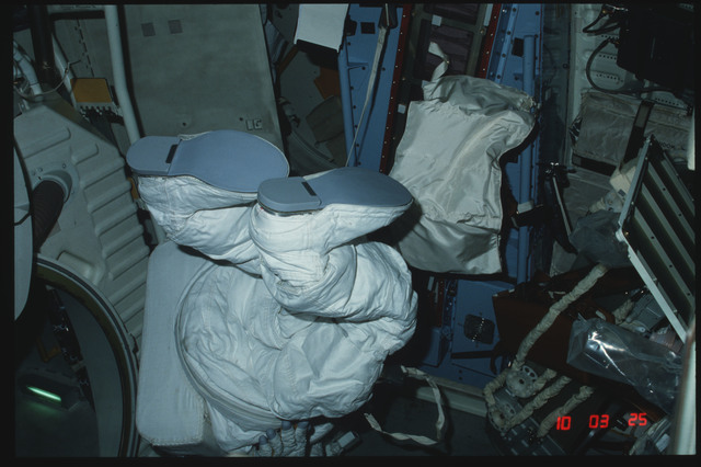 S04-24-155 - STS-004 - Unmanned EMU suit floats in front of open airlock hatch on middeck