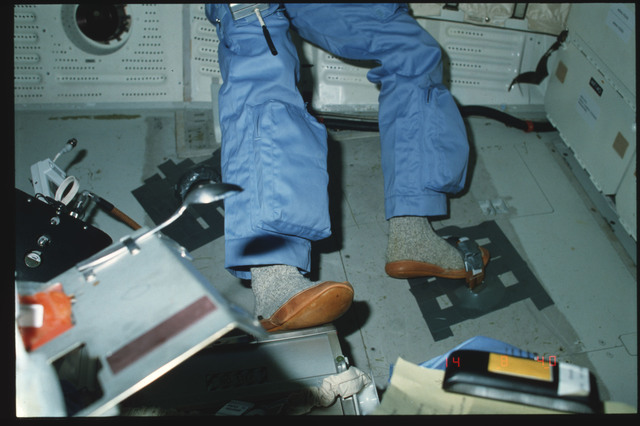 S05-07-240 - STS-005 - Commander Brand on port side middeck demonstrates IVA foot restraint