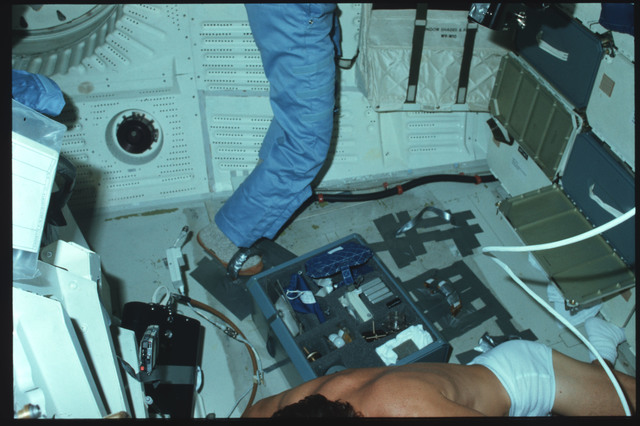 S05-15-570 - STS-005 - Crew members use IVA foot restraints and conduct experiment on middeck