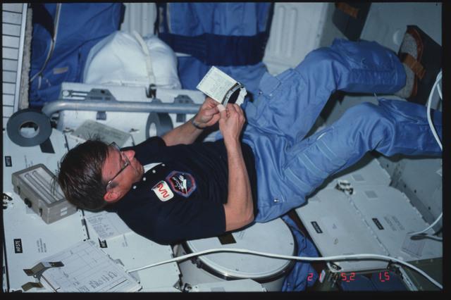 S06-06-462 - STS-006 - Commander Weitz adjusts EMU wrist cuff checklist on middeck