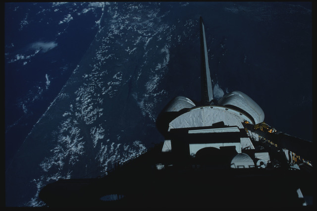 S07-11-501 - STS-007 - Earth Observations below shadowed PLB and vertical tail and OMS pods