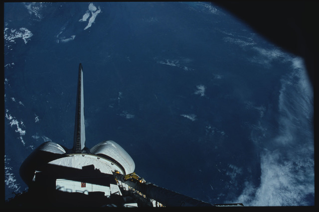 S07-11-503 - STS-007 - Earth Observations below shadowed PLB and vertical tail and OMS pods