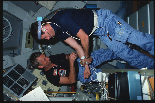 S09-05-143 - STS-009 - Astronauts Garriott and Lichtenberg conducting experiment in Spacelab
