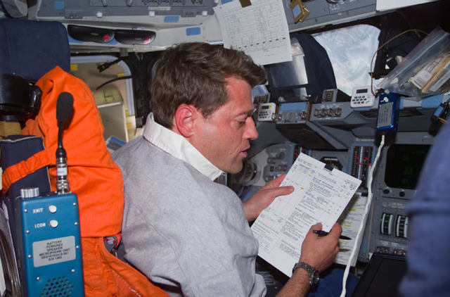 S100E5147 - STS-100 - Pilot Ashby reviews a checklist at the