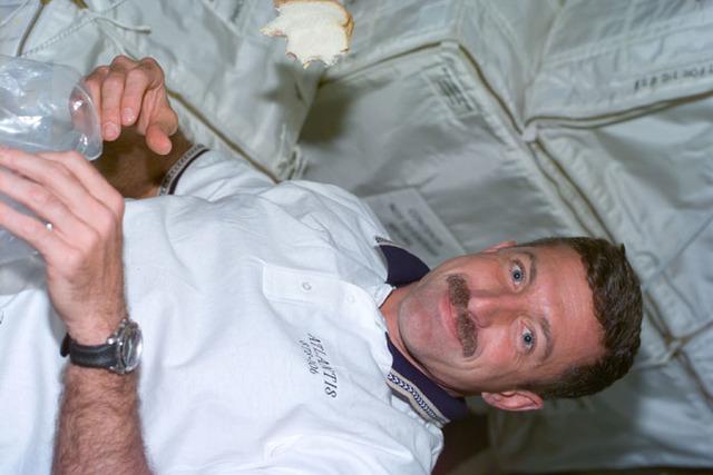 S106E5018 - STS-106 - MS Dan Burbank eats a sandwich aboard Atlantis during STS-106