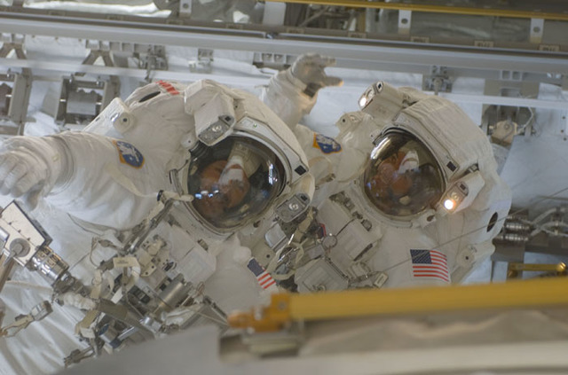 S110E5600 - STS-110 - Walheim and Smith wave to fellow crewmembers during the third EVA of STS-110
