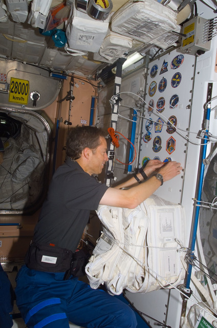 S113E05384 - STS-113 - Wetherbee places mission sticker on panel in Node 1 during STS-113 / EXP. 5