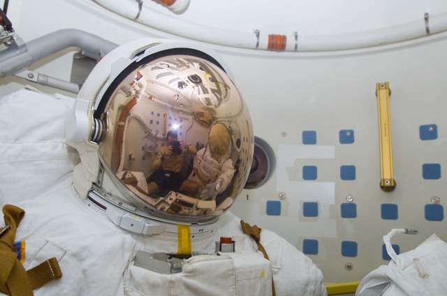 S113E05527 - STS-113 - Lopez-Alegria's reflection in EMU visor as he takes a photograph during STS-113