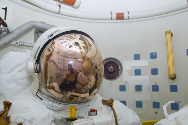 S113E05528 - STS-113 - Lopez-Alegria's reflection in EMU visor as he takes a photograph during STS-113