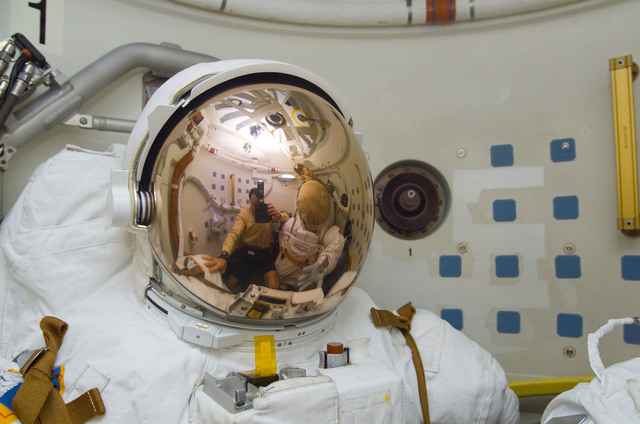 S113E05529 - STS-113 - Lopez-Alegria's reflection in EMU visor as he takes a photograph during STS-113