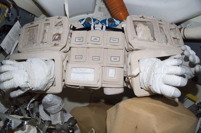 S114E6996 - STS-114 - EMU gloves in airlock