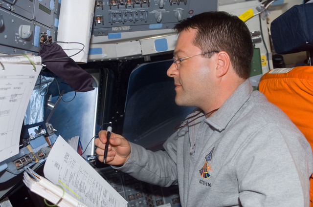 S116E05536 - STS-116 - STS-116 MS Patrick looks at crew procedures in the aft FD on Space Shuttle Discovery
