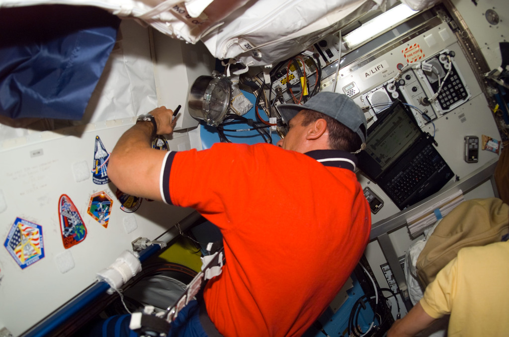 S116E05807 - STS-116 - STS-116 Pilot Oefelein signs STS-116 Patch in the Airlock