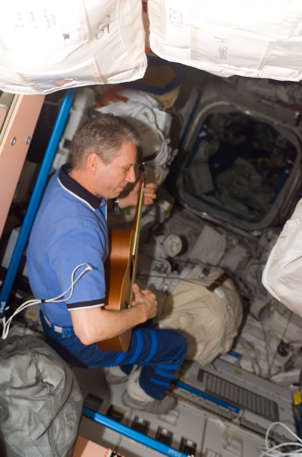 S116E06541 - STS-116 - STS-116 FE Reiter plays guitar in the Node 1 during Joint Operations