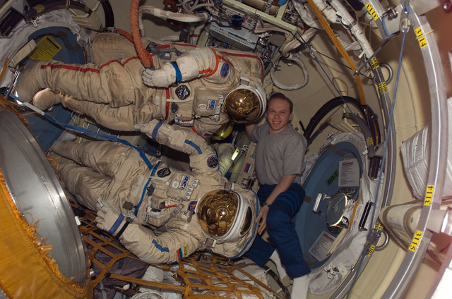 S117E07131 - STS-117 - Kotov poses with Russian Orlan Spacesuits in the Pirs DC1 during Joint Operations