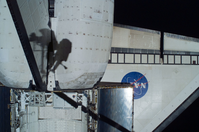 S121E06394 - STS-121 - EVA crewmembers shadows on the port OMS pod taken on EVA1 during STS-121 / Expedition 13 joint operations