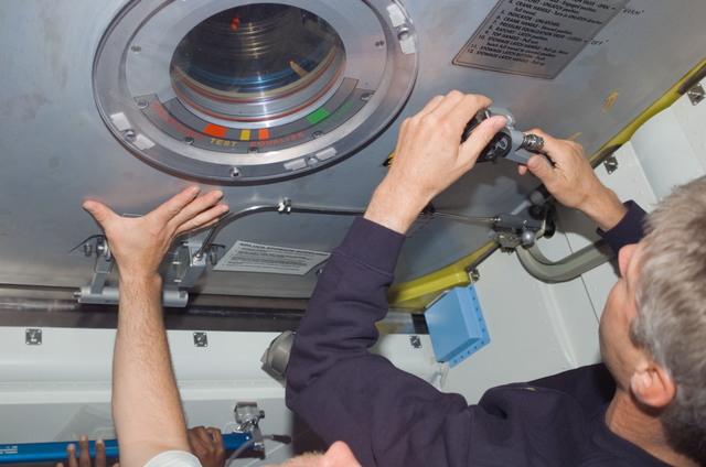 S121E06490 - STS-121 - Kelly and Reiter close the Crew Lock hatch in preparation for EVA3 during STS-121 / Expedition 13 joint operations