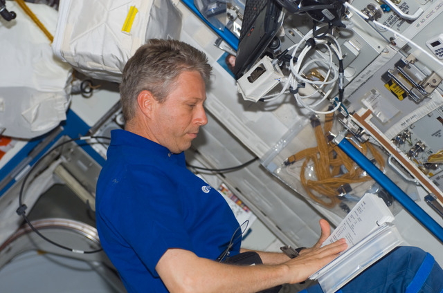 S121E07237 - STS-121 - Reiter reads procedures while working in the U.S. Lab during STS-121 / Expedition 13 joint operations