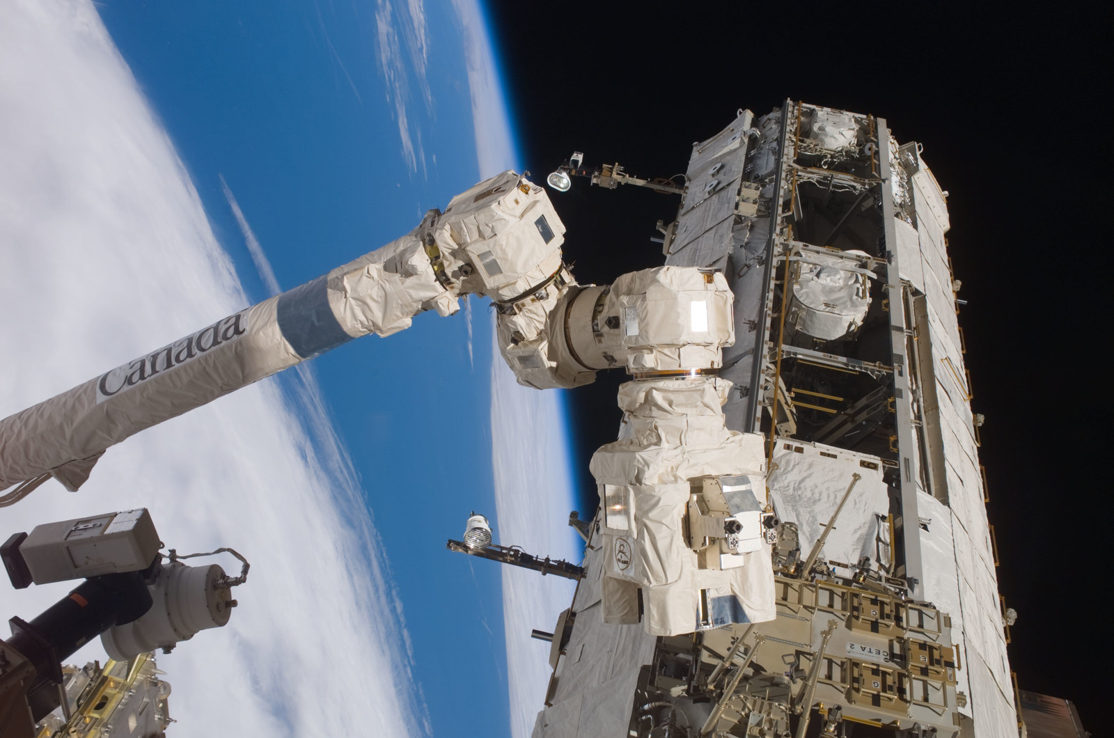 S121E07339 - STS-121 - The SSRMS positions to grapple with the MBS during STS-121 / Expedition 13 joint operations