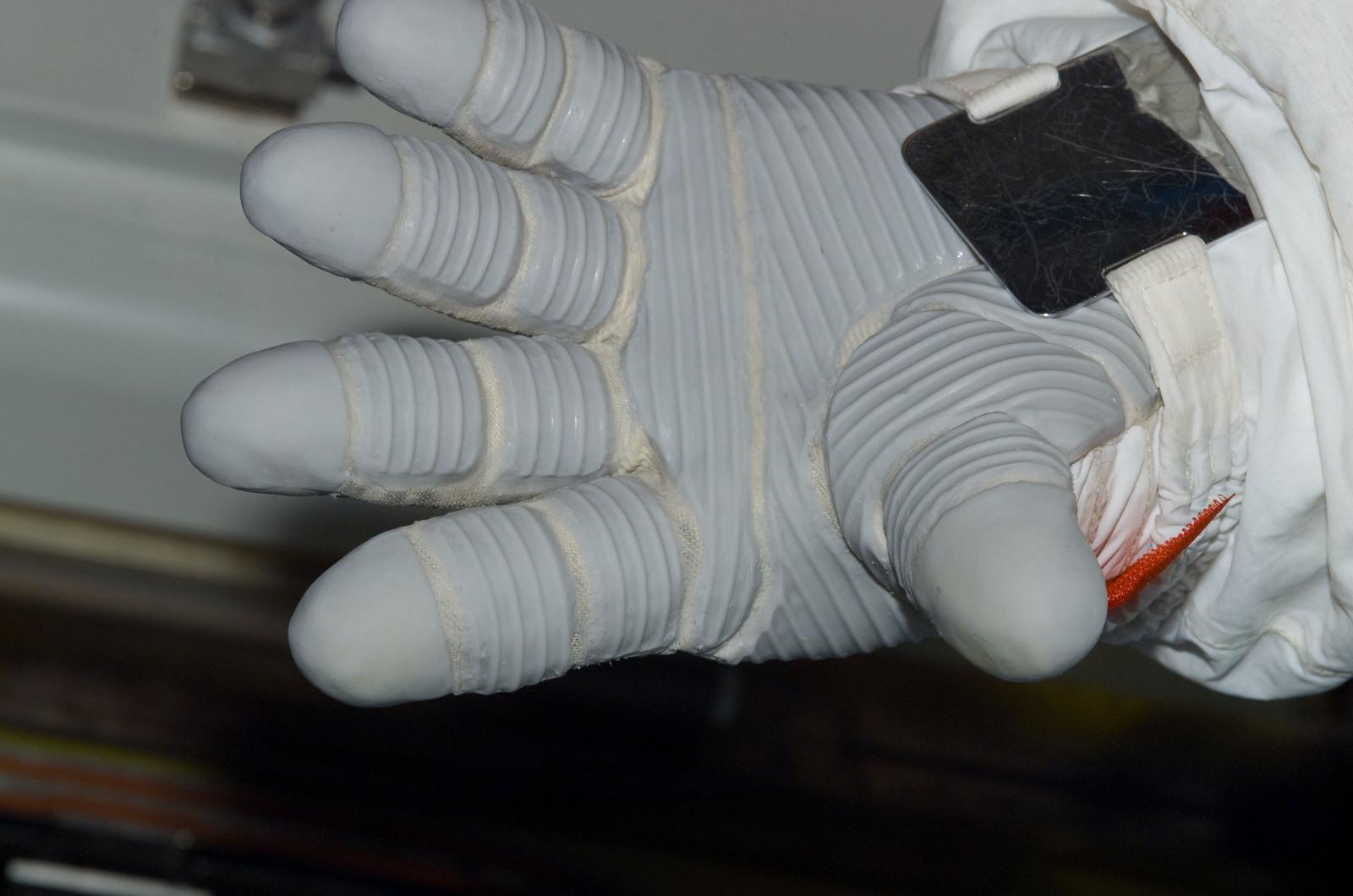 S122E008705 - STS-122 - Inspection of EMU Glove after EVA 3