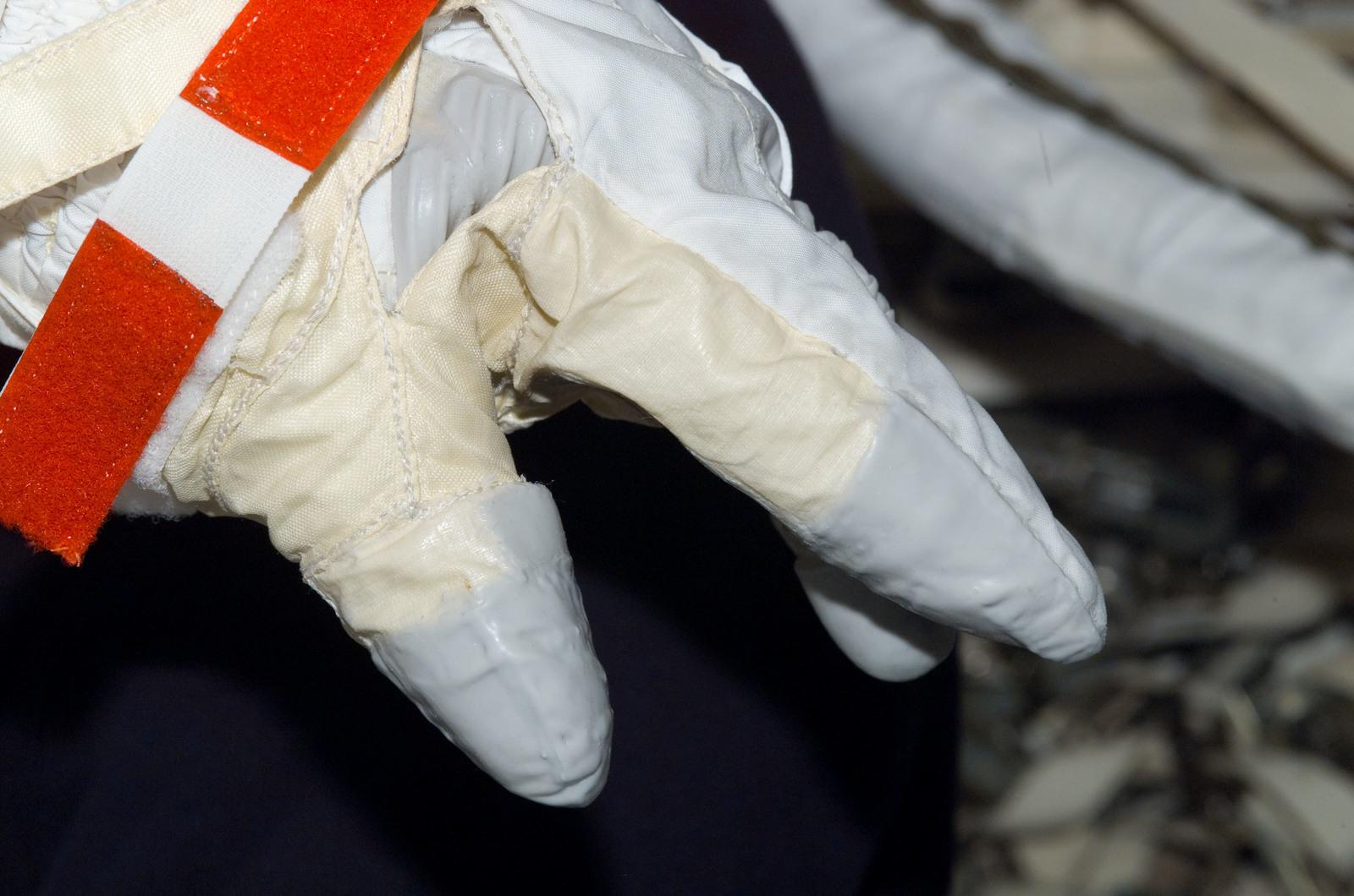 S122E008716 - STS-122 - Inspection of EMU Glove after EVA 3