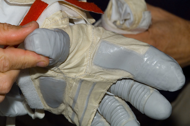 S122E008720 - STS-122 - Inspection of EMU Glove after EVA 3