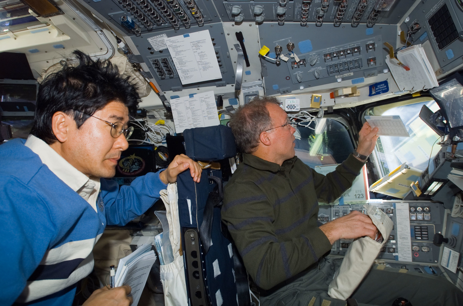 S123E005634 - STS-123 - Gorie looks at crew procedures in the aft FD during STS-123 mission