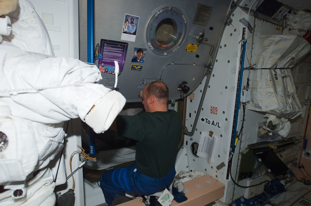 S123E006398 - STS-123 - Reisman working in the Node 1 hatch area during Joint Operations