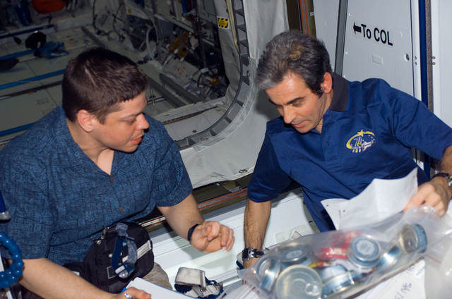 S123E009821 - STS-123 - Behnken and Eyharts look through crew procedures in the Node 2 during Joint Operations