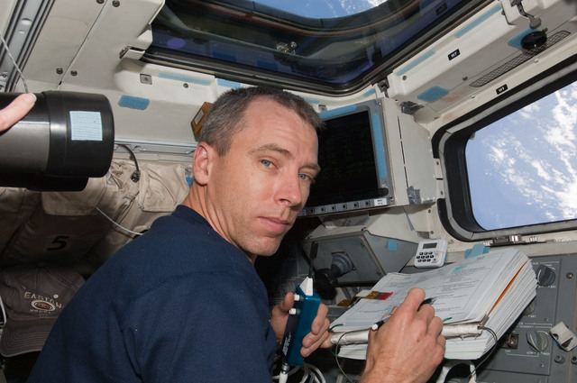 S125E009516 - STS-125 - STS-125 MS5 Andrew Feustel works on the Flight Deck during Flight Day 7